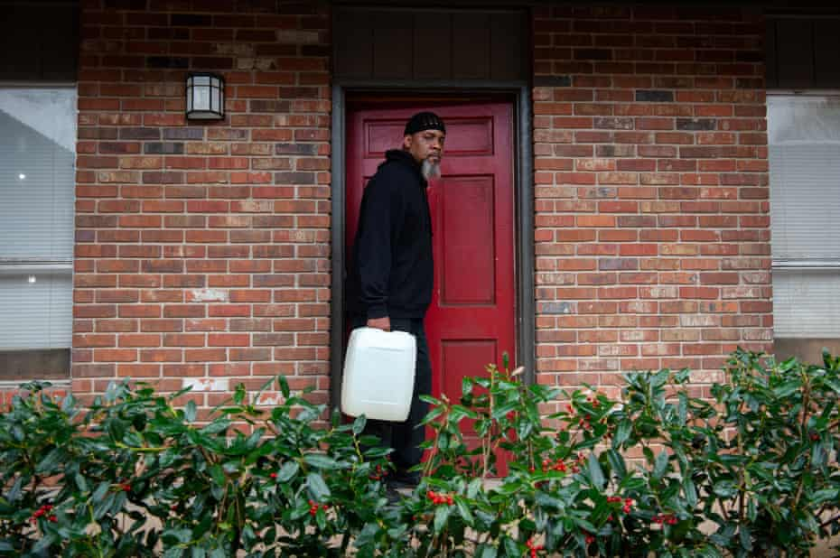 Roderick Readus carries a reusable water container outside his apartment in Jackson, Mississippi on March 2, 2021. Photo by Rory Doyle for The Guardian.