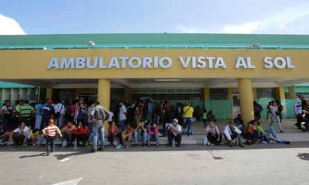 People gather outside a health center as they wait to get treatment for malaria, in San Felix, Venezuela