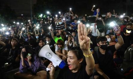 Para pengunjuk rasa memberi hormat tiga jari di luar kantor polisi Prachachuen di Bangkok