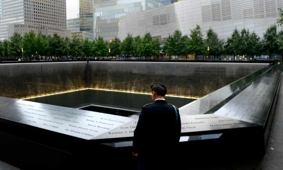 A member of the US military looks out at the South Pool at the National September 11 Memorial, in downtown Manhattan.