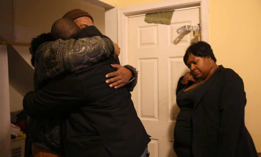 Bettie Jones's brothers Melvin Jones, in hat, and Robin Andrews hug in their sister's living room.