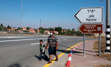 A Palestinian man and his son walk near the Israeli settlement of Yattir in the West Bank.