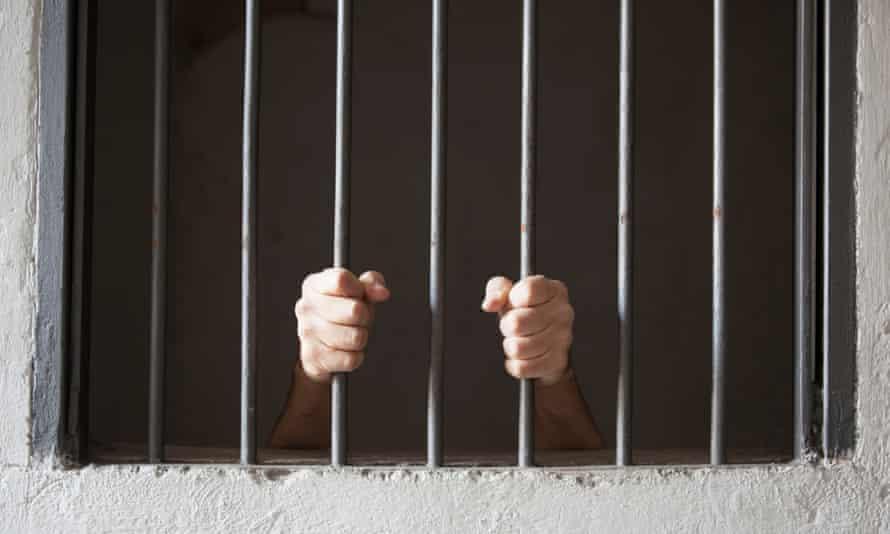 A prisoner grips cell bars