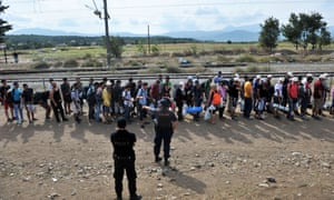 Migrants and refugees wait to cross the Greek-Macedonia border near the village of Idomeni, in northern Greece .