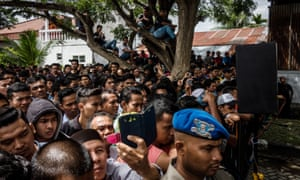 Acehnese people attend the public caning of two young gay men who are said to have violated Sharia law.