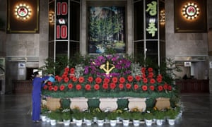 A hotel worker waters a flower display laid for the country's big party. North Korea