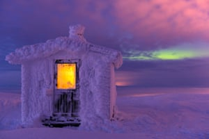 Hoarfrost-covered cabin at dusk, with northern lights in the background in Dundret nature reserve, Swedish Lapland.