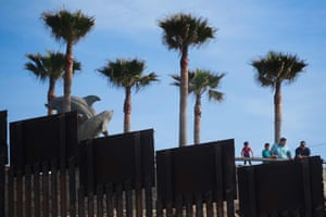 People in Tijuana, Mexico, look over the border fence separating the beaches at Border Field State Park