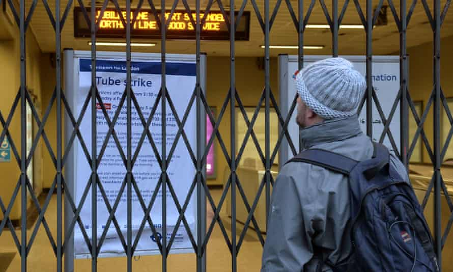 A man looks through locked gates at London Bridge station, London, at a notice about the tube strike