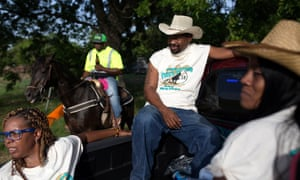 "Sonya Jernigan, Derek Reed and Shaniqua Johnson in the back of a pickup truck at the trail ride. Darryl ""Dingo"" Browning moderates riders on his horse at the trail ride in the background."