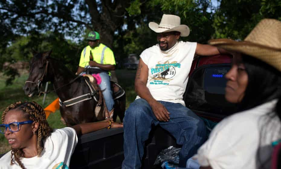 """Sonya Jernigan, Derek Reed and Shaniqua Johnson in the back of a pickup truck at the trail ride. Darryl """"Dingo"""" Browning moderates riders on his horse at the trail ride in the background."""