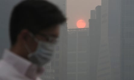 A man in Singapore wears a mask against air pollution as the sun sets among buildings covered with haze.
