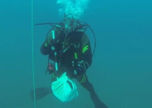 A Guardia Civil diver with one of the bundles of human remains