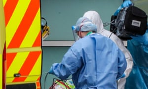 Health workers in PPE deal with an ambulance arrival