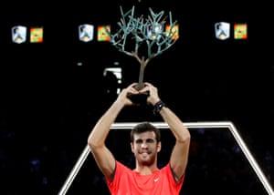 Karen Khachanov celebrates with the trophy after winning the final against Novak Djokovic.