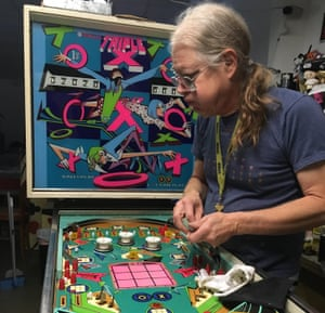Tim Arnold works on the Triple X machine at his pinball hall of fame.