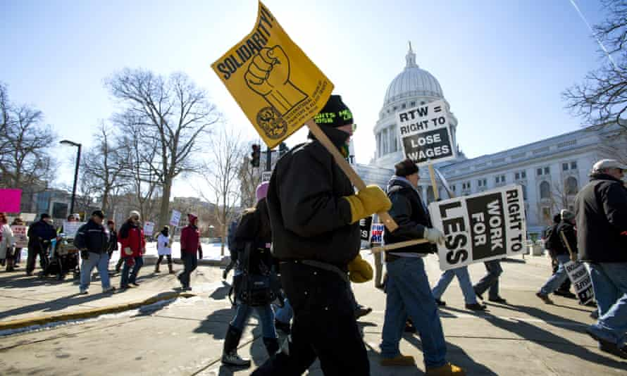 """Protesters march around the Capitol after participating in a rally against a """"right-to-work"""" proposal, on Saturday, Feb. 28, 2015, in Madison, Wis. Thousands of Wisconsin union workers rallied at the Capitol Saturday to protest a """"right-to-work"""" proposal that would outlaw the mandatory payment of union dues, but the crowd was much smaller than those in 2011 against Gov. Scott Walker's law stripping public sector unions of much of their power. (AP Photo/Wisconsin State Journal, Steve Apps)"""