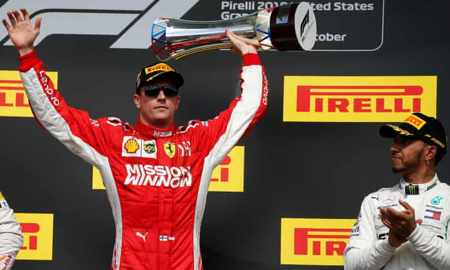 Kimi Räikkönen holds up the winning trophy as Lewis Hamilton applauds. It was the Finnish driver's first race win since 2013.