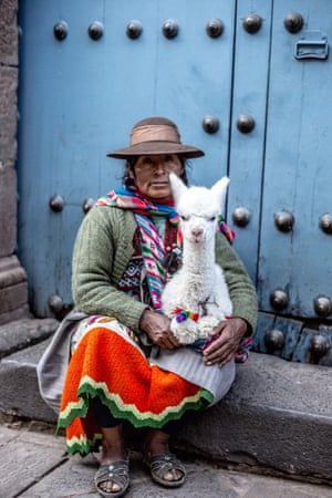 Peruvian woman and baby  llama.  Photographer: Eddie Hart: In the cobbled streets off Cusco's main square, I came across this woman sitting in the doorway of a crumbling colonial building. Her colourful clothing caught my attention, and who can resist petting an adorable baby llama?