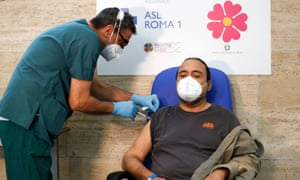 A health worker administers a booster dose of a coronavirus vaccine to patient Ivano Arcangeli, as vaccinations jump in Italy.