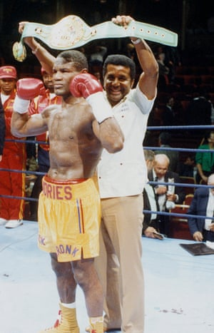Dennis Andries poses with his WBC light heavyweight world title belt held up by trainer Manuel Stewart before Andries successfully defended his title against Sergio Daniel Merani with a TKO in the 4th round of their October 1990 fight.