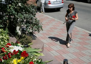 A woman places flowers to pay tribute to the victims of the Bastille Day truck attack in Kiev