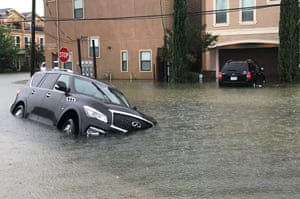 A car sits half submerged in a residential area of Houston.