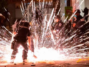 A firecracker thrown by protesters explodes under police a block from the White House