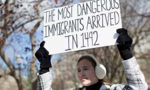 A protester holds a sign near the White House to protest President Donald Trump's travel ban.