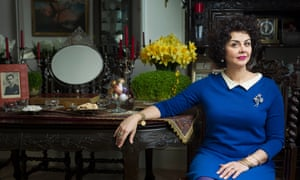 Kamin Mohammadi wearing a blue dress and sitting by a table