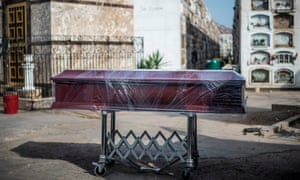 A coffin containing the body of a Covid-19 victim is wrapped in clingfilm before cremation at El Angel crematorium in Lima, Peru.