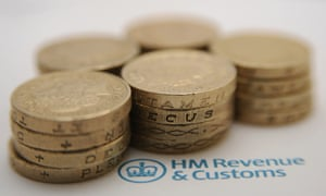Pound coins on a piece of paper featuring the HMRC logo