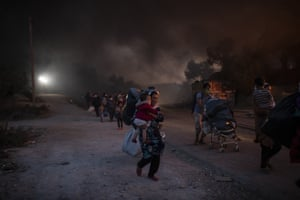 Migrants flee from the Moria refugee camp during a second fire on the northeastern Aegean island of Lesbos.