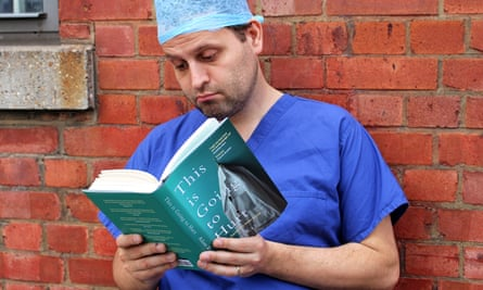 A man in surgeon's 'scrubs' leans against a brick wall reading the medical book This Is Going To Hurt.
