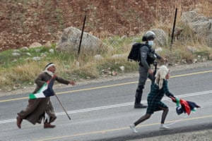 A Palestinian demonstrator runs after an Israeli settler who is taking away Palestinian flags in Kafr Malik, West Bank