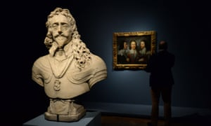 a visitor looks at Charles I in Three Positions by Anthony van Dyck by a statue of the king by Francois Dieussart at the Royal Academy exhibition Charles I: King and Collector.