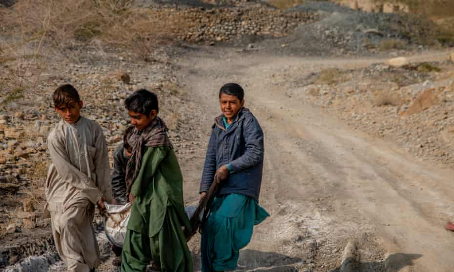 Kids carrying a sack of coal to sell on the main road in Mach, Balochistan.