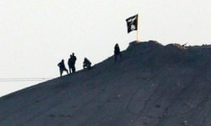 Militants with the Islamic State group are seen after placing their group's flag on a hilltop at the eastern side of the town of Kobani, Syria.