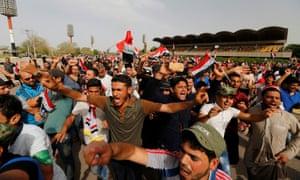 Supporters of Moqtada al-Sadr wave flags