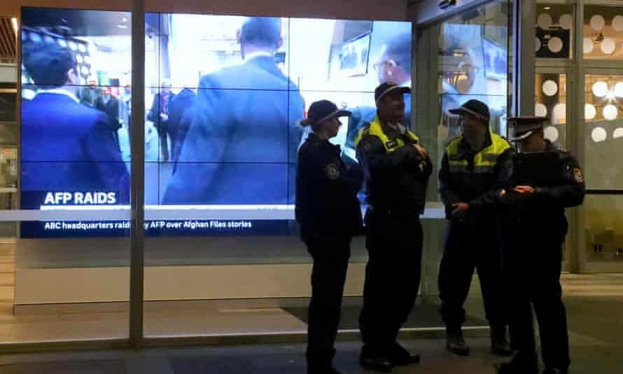 Police stand in front of a television screen at the ABC offices