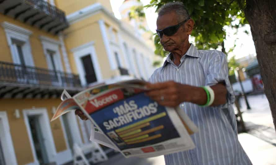 José Vásquez reads a newspaper with a Spanish headline that reads, 'More sacrifices', a day after Puerto Rico's governor, Alejandro García Padilla, gave a speech about the territory's $72bn debt.