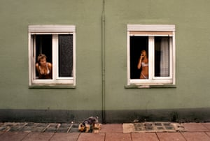 Sex workers keeping a lookout for their pet terrier playing outside their brothel which faced the Krupp works, Rhur Valley, Germany, 1985