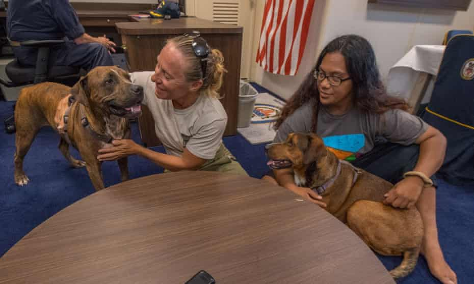 Jennifer Appel, left, and Tasha Fuiava, with their dogs Zeus, left, and Valentine, take questions in the captain's cabin of the USS Ashland.