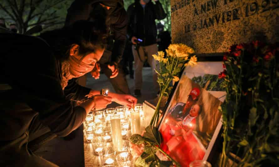 A person lights a candle during a vigil following the fatal police shooting of Daunte Wright in Minnesota.