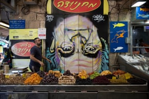 A shop owner works next to an upside-down image of David Ben-Gurion, Israel's first prime minister