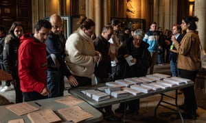 People take ballots before casting their vote at a polling station on April 28, 2019 in Barcelona, Spain.