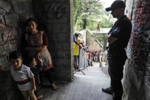A migrant child waves at police officer as families wait in a queue