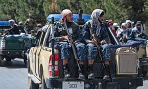 Taliban fighters patrol a street in Kabul.