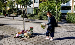 A woman lays flowers near the home of the murdered lawyer Derk Wiersum in Amsterdam