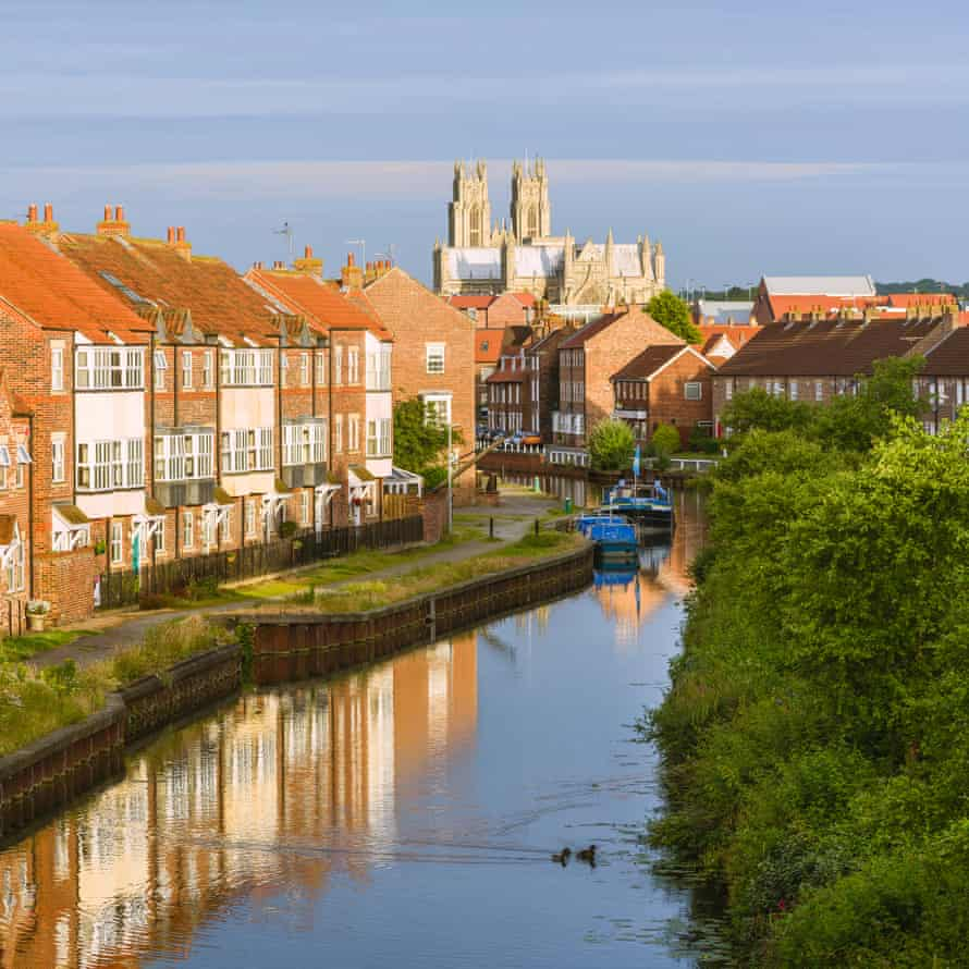 The ancient minster, town houses, and the beck (canal) with barges at sunrise on a peaceful summer morning in Beverley, Yorkshire